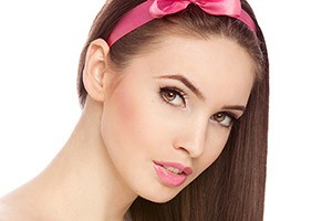 Portrait of a fresh and lovely woman with pink bow